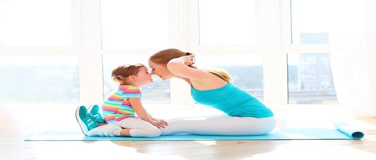 赤ちゃんと一緒にトレーニングしている産後のママ