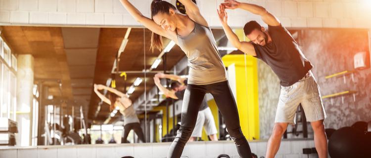 トレーニングジムでストレッチをしている男女