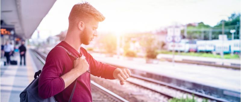 時間を確認しながら電車を待つ男性
